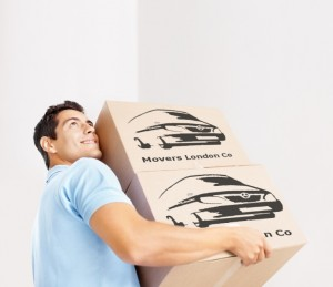 Moving in apartment - Smiling young man carrying cardboard boxes